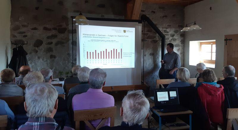 Dr. Johannes Franke zeigt Diagramme zum Klimawandel in Sachsen